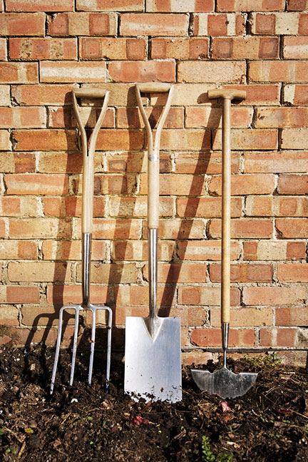 three garden tools leaning against a brick wall